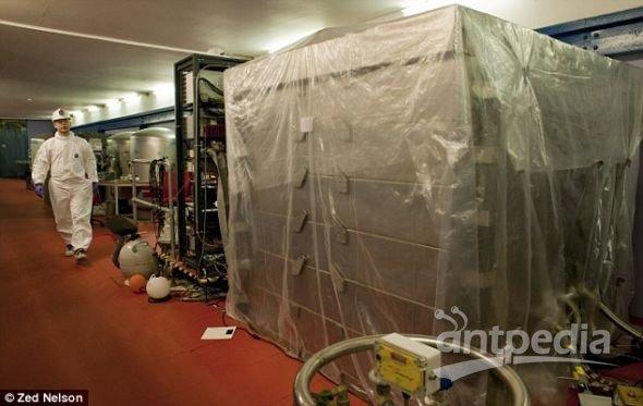 天体粒子物理学家帕维尔・马耶夫斯基走进被塑料布包裹的ZEPLIN-III探测器